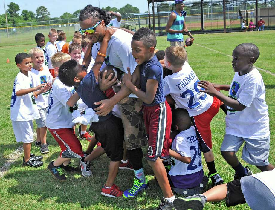 Seattle Seahawks safety Earl Thomas, right, is holding his second annual youth football camp on Friday and Saturday of this week. Here he is working with some of the smaller kids who were trying to bring him down. Friday's camp ran from 8 a.m. to 2 p.m., at West Orange-Stark High School. On Saturday, in addition to the workout for kids, adult teams, including one with Earl, will play in a 7-on-7 football tournament beginning a 1 p.m.. Dave Ryan/The Enterprise