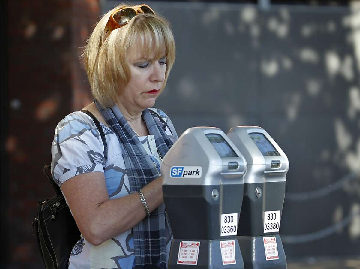 Sandra Barrios feeds a parking meter on The Embarcadero in San Francisco, Calif. on Friday, June 28, 2013. The violation for parking at expired meters jumps to $74 on July 1, making it the most expensive fine in the country.
