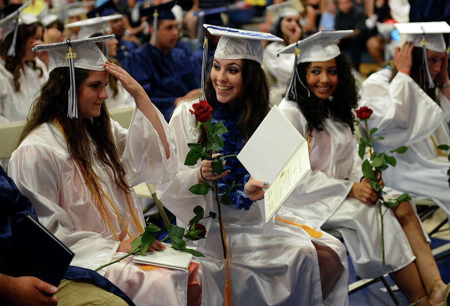 Graduate Kaitlyn Hennessey proudly shows her classmates her diploma during Ansonia High School's Commencement Exercises in Ansonia, Conn. on Friday June 28, 2013. Photo: Christian Abraham / Connecticut Post