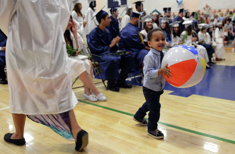 Jestin Ayala, 5, grabs a beach ball tossed by graduates during Ansonia High School's Commencement Exercises in Ansonia, Conn. on Friday June 28, 2013. Jestin was there to see his sister Yaresa graduate. Photo: Christian Abraham / Connecticut Post