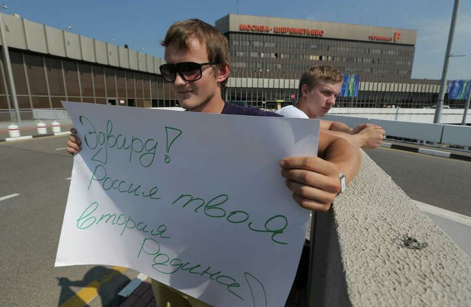 A supporter of National Security Agency leaker Edward Snowden holds a poster outside Sheremetyevo airport in Moscow Friday, June 28, 2013.  Russian and foreign journalists continued to monitor the Sheremetyevo international airport, where Snowden is believed to remain at the transit zone. The poster reads : Edward! Russia is your second Motherland!  (AP Photo/Sergei Grits) Photo: Sergei Grits, STF / AP