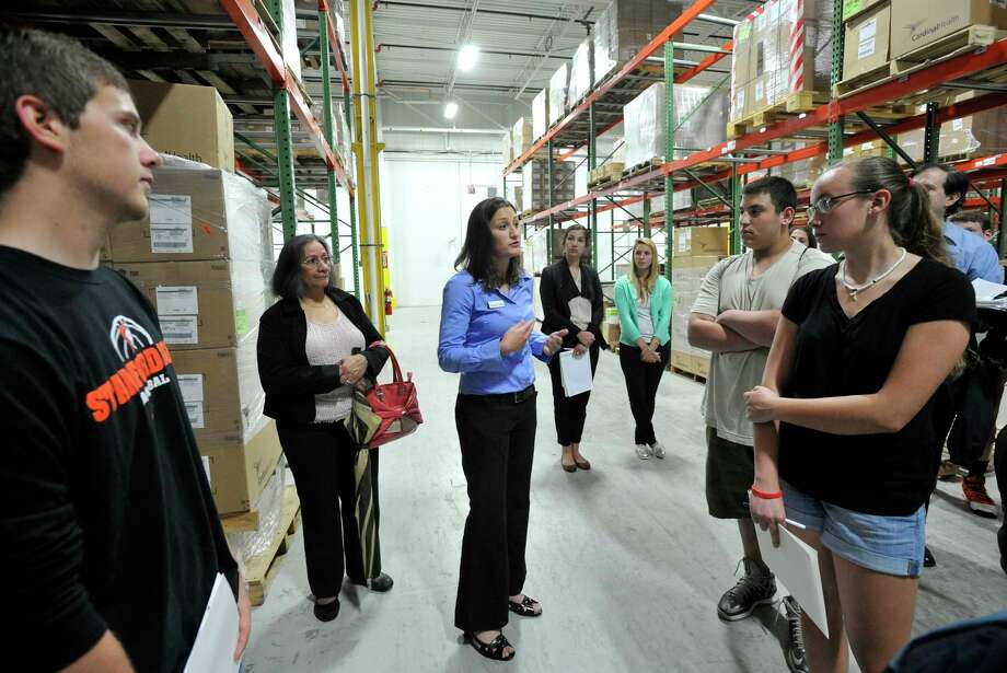 Kate Dischino, emergency response manager for AmeriCares, speaks to Stamford High School students during their visit to the humanitarian relief organization's headquarters and warehouse in Stamford on Monday, June 10, 2013. Dischino graduated from Stamford High School in 2000. Photo: Jason Rearick / Stamford Advocate
