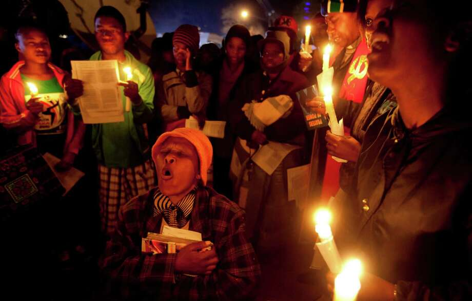 Well-wishers sing and pray Friday for the health of Nelson Mandela outside the Mediclinic Heart Hospital, where former South African President Nelson Mandela is being treated in Pretoria, South Africa. Photo: Ben Curtis, STF / AP