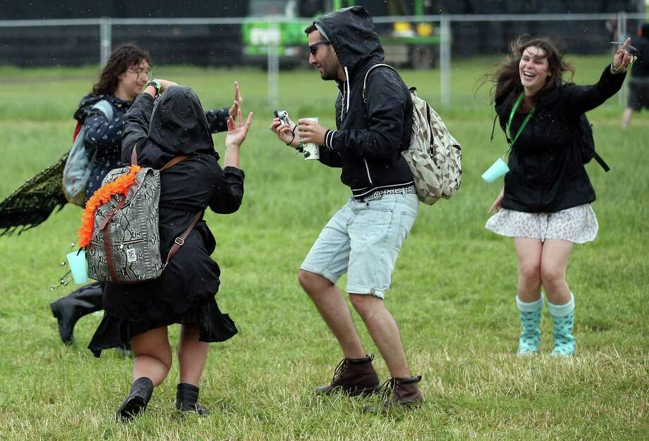 GLASTONBURY, ENGLAND - JUNE 27:  Festival goers dance in the rain at the Glastonbury Festival of Contemporary Performing Arts site at Worthy Farm, Pilton on June 27, 2013 near Glastonbury, England. Gates opened on Wednesday at the Somerset Diary Farm that will be playing host to one of the largest music festivals in the world and this year features headline acts Artic Monkeys, Mumford and Sons and the Rolling Stones. Tickets to the event which is now in its 43rd year sold out in minutes and that was before any of the headline acts had been confirmed. The festival, which started in 1970 when several hundred hippies paid 1 GBP to watch Marc Bolan, now attracts more than 175,000 people over five days. Photo: Matt Cardy, Getty Images / 2013 Getty Images