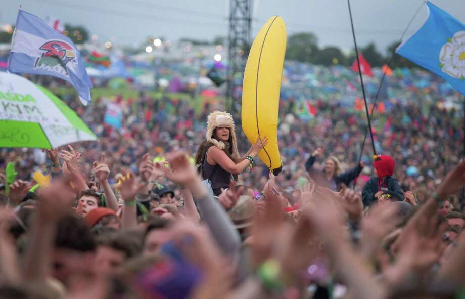 A woman holds an inflatable banana as she watches Dizzee Rascal perform on the Pyramid main stage at Glastonbury, England, Friday, June 28, 2013. Thousands of music fans have arrived for the festival to see headliners, Arctic Monkeys, Mumford and Sons and the Rolling Stones. Photo: Joel Ryan, Associated Press / Invision