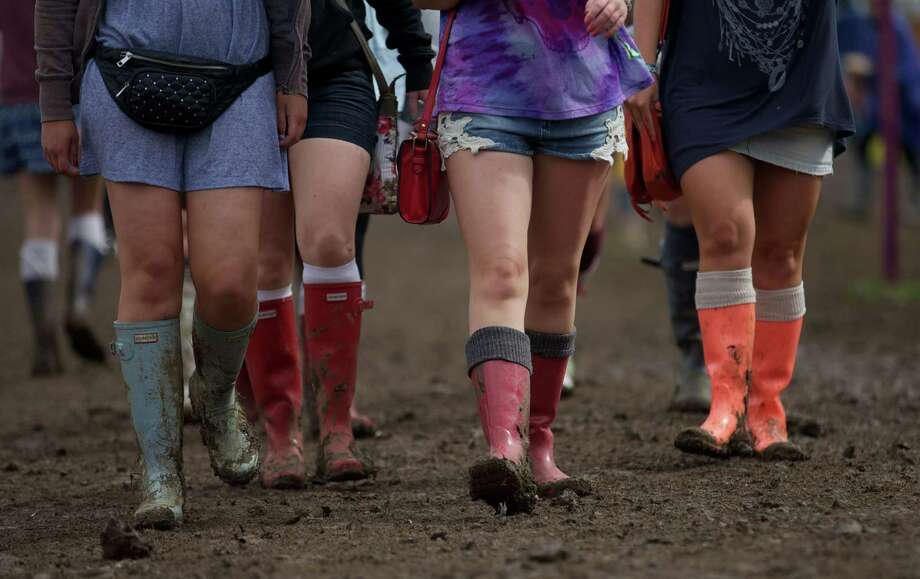 Festival goers in rubber boots walk across the site on third day of the Glastonbury Festival of Contemporary Performing Arts near Glastonbury, southwest England on June 28, 2013. The festival attracts 170,000 party-goers to the dairy farm in Somerset, and this year's tickets sold out within two hours of going on sale. The Rolling Stones will perform at the festival for the first time, headlining on Saturday night. Photo: ANDREW COWIE, AFP/Getty Images / AFP