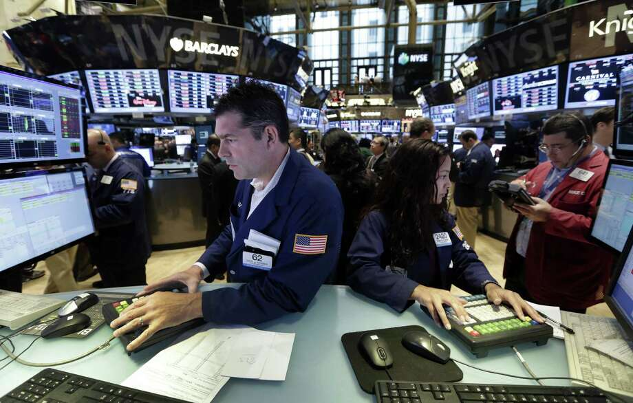 Specialists David Haubner and Wingszi Cihang work on the floor of the New York Stock Exchange on Friday. Despite a rocky June, the S&P 500 rose 13.8 percent in the first half of the year, when dividends are added. Photo: Richard Drew / Associated Press