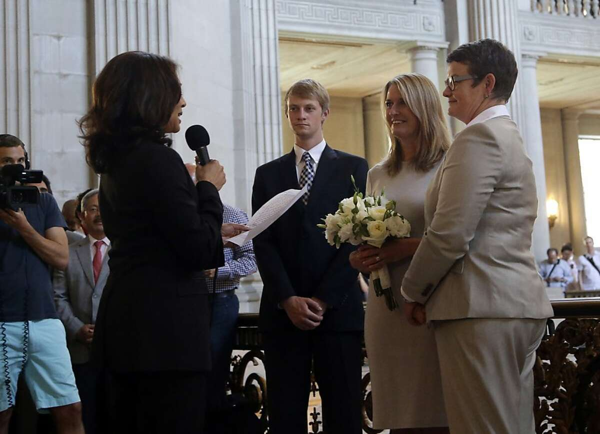 Sandy Stier, center left, and Kris Perry, at right, exchange wedding vows in front of California Attorney General Kamala Harris, left, at City Hall in San Francisco, Friday, June 28, 2013. Stier and Perry, the lead plaintiffs in the U.S. Supreme Court case that overturned California's same-sex marriage ban, tied the knot about an hour after a federal appeals court freed same-sex couples to obtain marriage licenses for the first time in 4 1/2 years. (AP Photo/Marcio Jose Sanchez)
