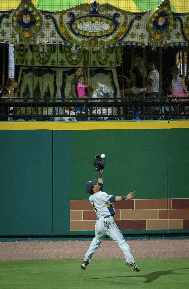 York Revolution outfielder Eric Patterson makes a catch in front of the carousel in left field during a game against the Sugar Land Skeeters at Constellation Field on Thursday, June 27, 2013, in Sugar Land. Photo: Smiley N. Pool, Houston Chronicle / © 2013  Smiley N. Pool