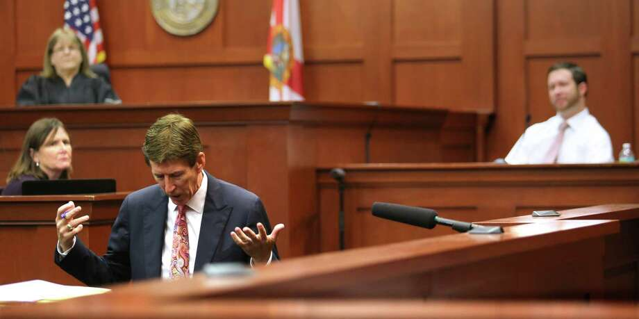 Defense attorney Mark O'Mara drops to his knees to make a point on Friday during the questioning of eyewitness Jonathan Good, right, at the George Zimmerman murder trial in Sanford, Fla. Photo: Joe Burbank, POOL / Pool Orlando Sentinel