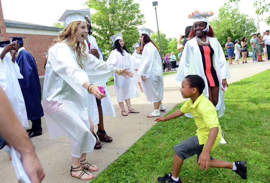 Stefan Winston, 5, rushes up to hug graduate Alyssa Korik before the start of Ansonia High School's Commencement Exercises in Ansonia, Conn. on Friday June 28, 2013. Photo: Christian Abraham / Connecticut Post