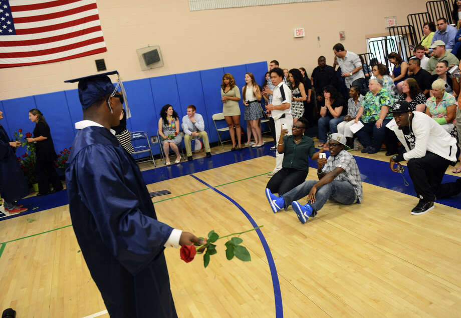 Graduate Epharim Collins stops to pose for a photo taken by family during Ansonia High School's Commencement Exercises in Ansonia, Conn. on Friday June 28, 2013. Photo: Christian Abraham / Connecticut Post