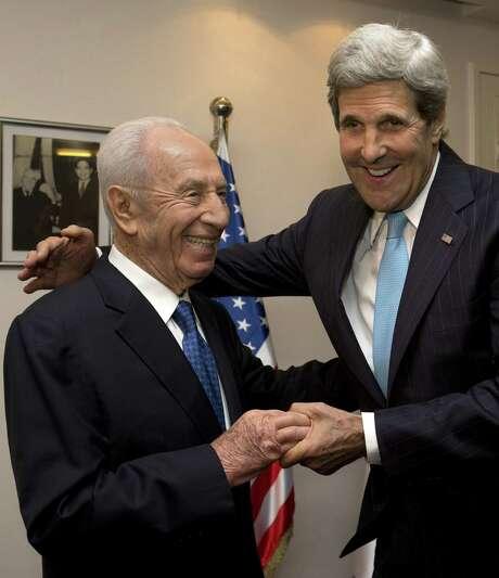 U.S. Secretary of State John Kerry (right) embraces Israeli President Shimon Peres. Photo: Jacquelyn Martin / Associated Press