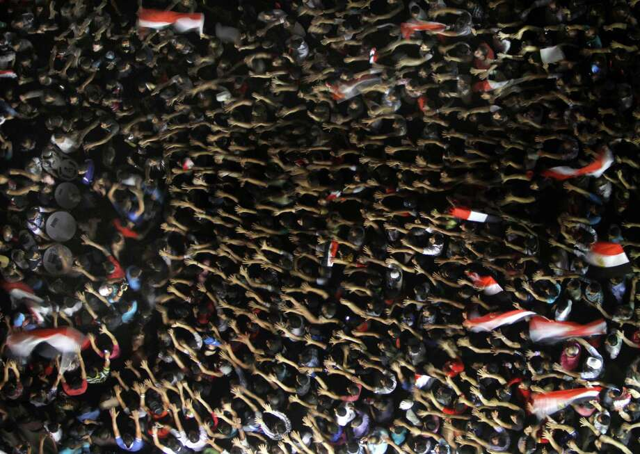 Protesters create a sea of waving arms and flags during a demonstration against Egyptian President Mohammed Morsi in Tahrir Square in Cairo. Photo: Amr Nabil / Associated Press