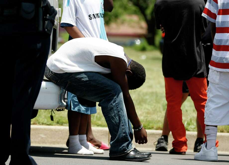 A family member appears in shock after the body  of 5-year-old Sida Osman was discovered in the  backyard of a house in Fort Worth. Photo: Khampha Bouaphanh, MBI / The Fort Worth Star-Telegram