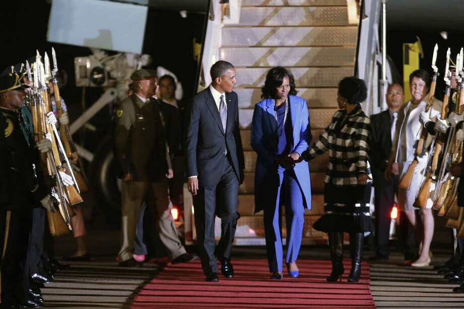 President Barack Obama and first lady Michelle Obama, greeted by South African officials  upon arriving, may or may not see Nelson Mandela, who is hospitalized in critical condition. Photo: Chip Somodevilla / Getty Images