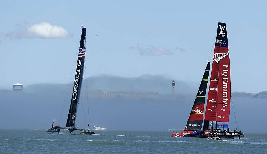 Oracle Team USA (left) and Emirates Team New Zealand sail near Alcatraz Island in the fog during training last month.  Louis Vuitton Cup races begin Sunday. Photo: Eric Risberg, Associated Press