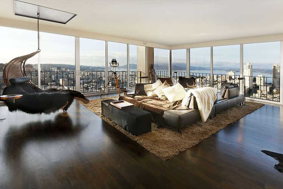 The co-op features a great room with hardwood floors and floor-to-ceiling windows. Photo: Steph Dewey/Reflex Imaging