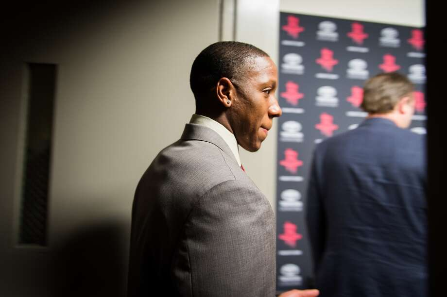 Isaiah Canaan, the 34th pick of the NBA draft, follows Rockets general manager Daryl Morey into a press conference.