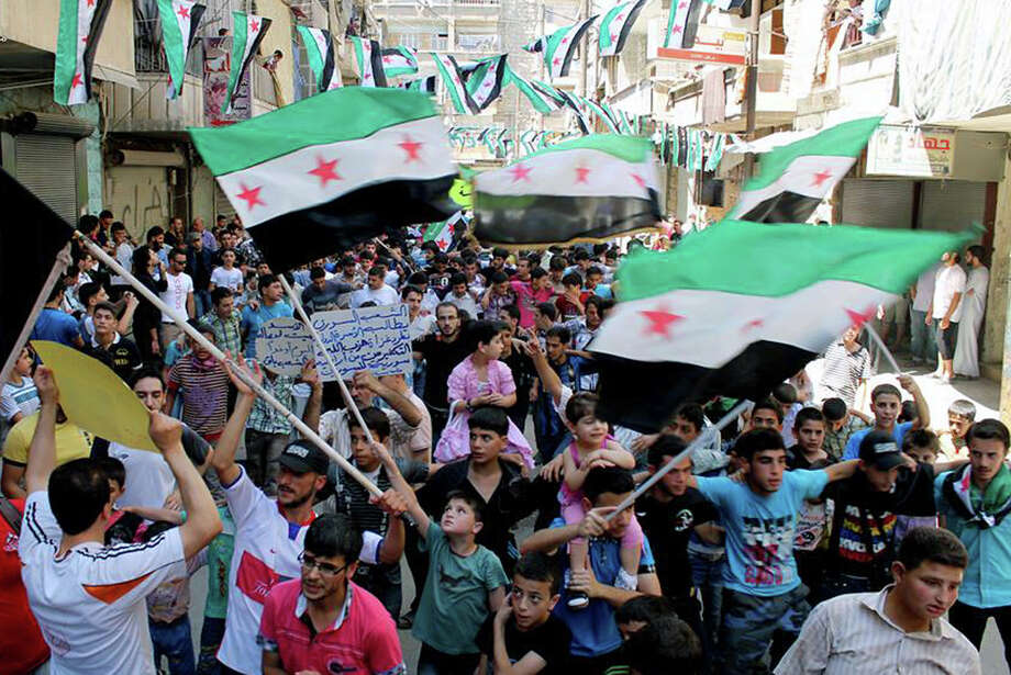 This citizen journalism image provided by Aleppo Media Center AMC which has been authenticated based on its contents and other AP reporting, shows anti-Syrian regime protesters holding Syrian revolution flags, during a demonstration in the neighborhood of Bustan Al-Qasr in Aleppo, Syria, Friday, June 28, 2013. Intense shelling by Syrian government troops on a village in the country's south killed several women and girls overnight as forces loyal to President Bashar Assad pushed ahead with an offensive against rebels near the border with Jordan, activists said Friday. (AP Photo/Aleppo Media Center AMC) Photo: HOEP / Aleppo Media Center AMC