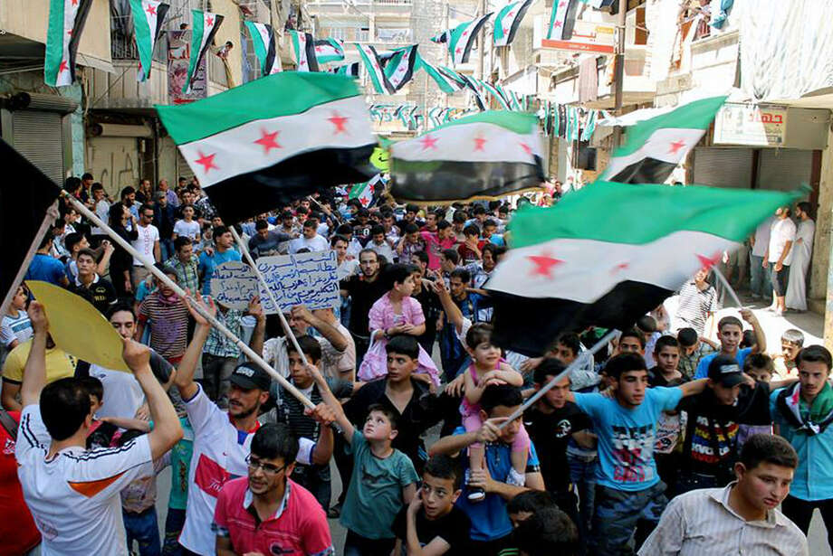 Anti-Syrian regime protesters hold Syrian revolution flags Friday during a demonstration in the neighborhood of Bustan Al-Qasr in Aleppo, Syria. Shelling by Syrian government troops on a village in the country's south killed several women and girls overnight. Photo: Aleppo Media Center / Associated Press