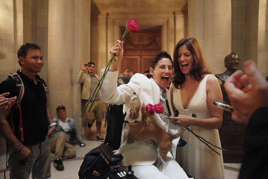 Frances Stevens (hand raised) and Jen Rainin (right ) react after being  married at City Hall by Bevan Dufty (hands at right corner), Director of HOPE, as Punum the dog stands on Stevens lap on Friday, June 28, 2013 in San Francisco,  Calif. Photo: Lea Suzuki, The Chronicle