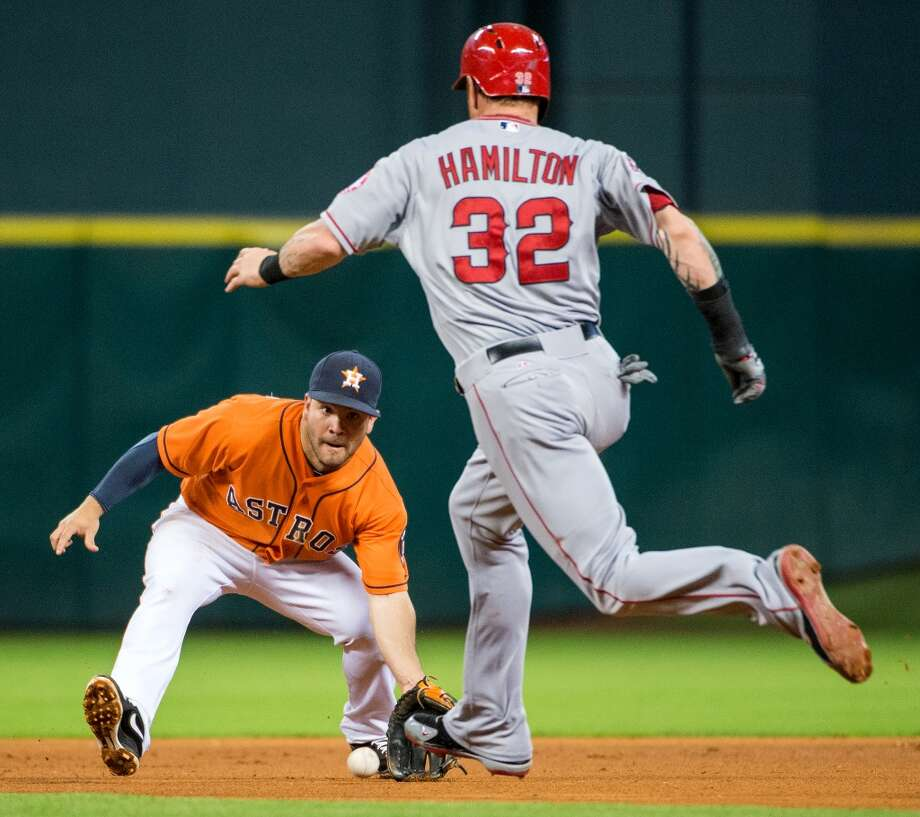 Astros second baseman Jose Altuve fields a grounder by Angels third baseman Alberto Callaspo before tagging Josh Hamilton to get the first out of a double play.