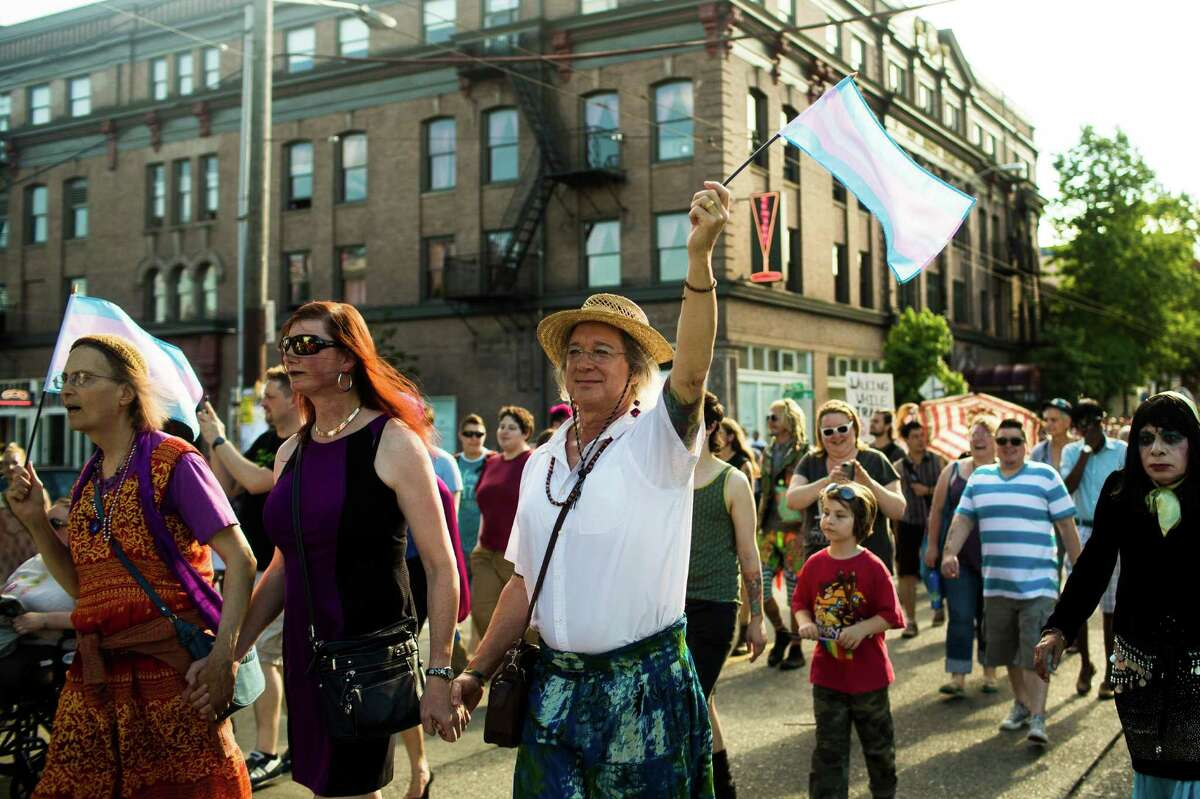 Waving flags and giving off an air of positivity, groups of attendees move down East Pike during the Trans Pride march and celebration Friday, June 28, 2013, in the Capitol Hill neighborhood of Seattle. The event intended to increase the power of the transgender community and its allies, both within and beyond Seattle.