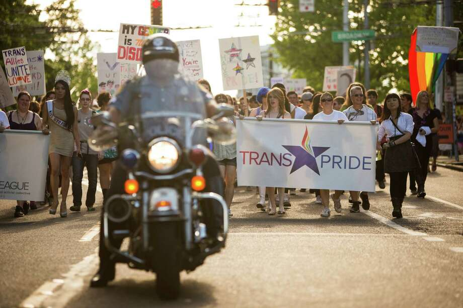 Waving flags and giving off an air of positivity, groups of attendees move down East Pike during the Trans Pride march and celebration Friday, June 28, 2013, in the Capitol Hill neighborhood of Seattle. The event intended to increase the power of the transgender community and its allies, both within and beyond Seattle. Photo: JORDAN STEAD, SEATTLEPI.COM / SEATTLEPI.COM