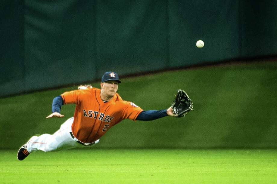 Astros center fielder Brandon Barnes makes a highlight-reel-worthy catch of a line drive hit by the Angels' J.B. Shuck for the final out of the third inning Friday night. The Astros went on to lose 4-2. Photo: Smiley N. Pool / © 2013  Smiley N. Pool