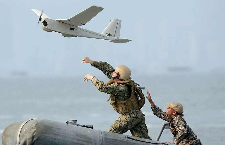 US (L) and Philippine navy personnel launch unmanned aerial vehicle (UAV) from a speed boat off the naval base in Sangley point, Cavite City, west of Manila on June 28, 2013, as part of the Cooperation Afloat Readiness and Training (CARAT) exercises. The six-day exercises involving three US Navy vessels, including the USS Fitzgerald, a guided missile destroyer are an annual event but this year they will be held off the west coast of the Philippines' main island of Luzon, close to Scarborough Shoal which China insists it owns. AFP PHOTO/TED ALJIBETED ALJIBE/AFP/Getty Images Photo: Ted Aljibe, AFP/Getty Images