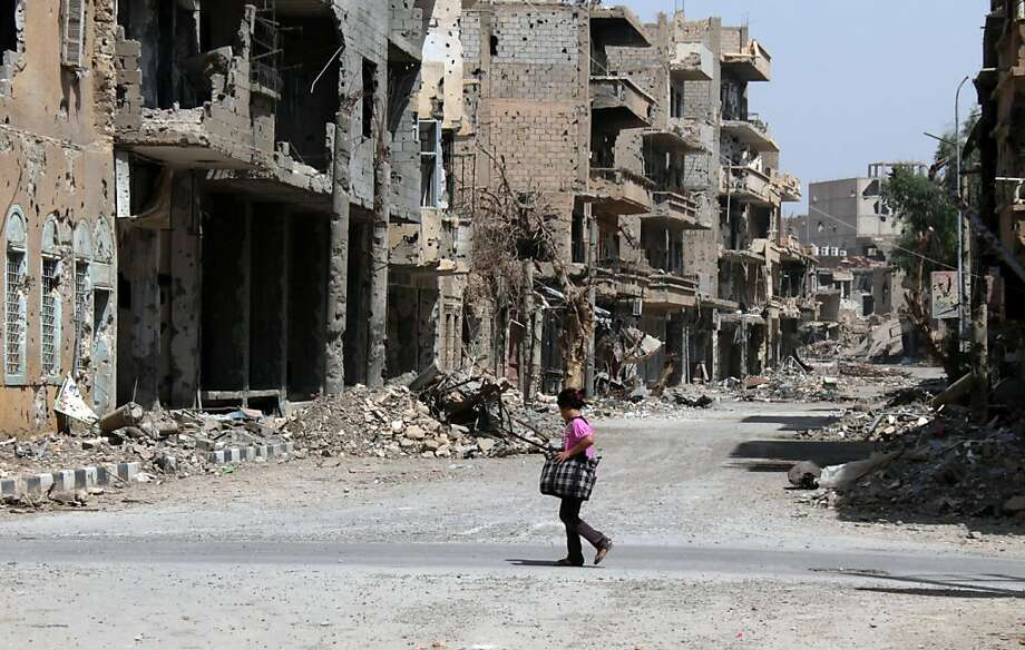A Syrian girl crosses the street holding a bag in the centre of Syria's northeastern city of Deir Ezzor on June 28, 2013. The Syrian Observatory for Human Rights watchdog, which relies on a network of contacts on the ground in Syria, said that more than 100,000 people, mainly civilians, have been killed since the uprising erupted. AFP PHOTO / ABO SHUJAABO SHUJA/AFP/Getty Images Photo: Abo Shuja, AFP/Getty Images