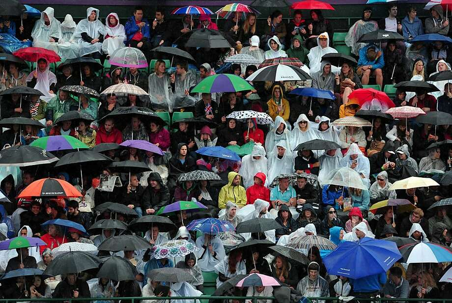 Spectators shelter under umbrellas as rain holds up play on the outdoor courts on day five of the 2013 Wimbledon Championships tennis tournament at the All England Club in Wimbledon, southwest London, on June 28, 2013. AFP PHOTO / CARL COURT CARL COURT/AFP/Getty Images Photo: Carl Court, AFP/Getty Images