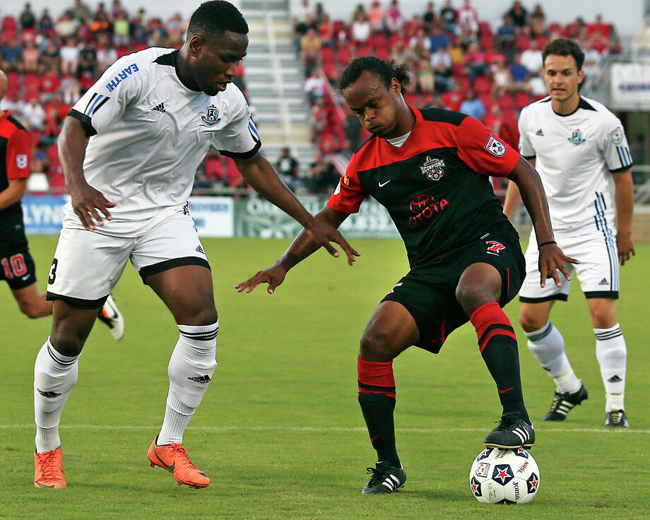 Stephen DeRoux dribbles in front of Edmonton's Edson Edward as the San Antonio Scorpions host FC Edmonton on June 22, 2013. Photo: For The San Antonio Express-News