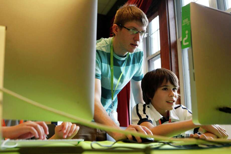 In this Wednesday, June 19, 2013 photo, instructor Thaddeus Owings, left, helps camper Nicholas Sanchez work on creating a video game while at an iD Tech Camp at the Emory University campus, in Atlanta. So-called coding camps for kids are becoming more popular amid a growing effort to expand access to computer programming and inspire more youths to seek computer science degrees and later careers in technology. (AP Photo/Jaime Henry-White) Photo: Jaime Henry-White, STF / AP