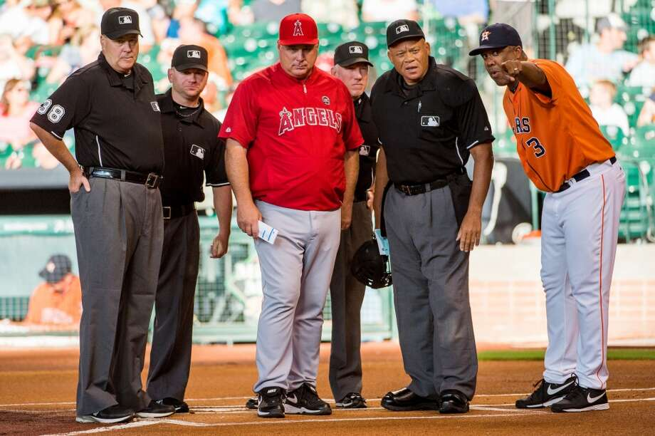 Astros bench coach Eduardo Perez (3) goes over the stadium ground rules with Angels manager Mike Scioscia and the umpire crew before the game.