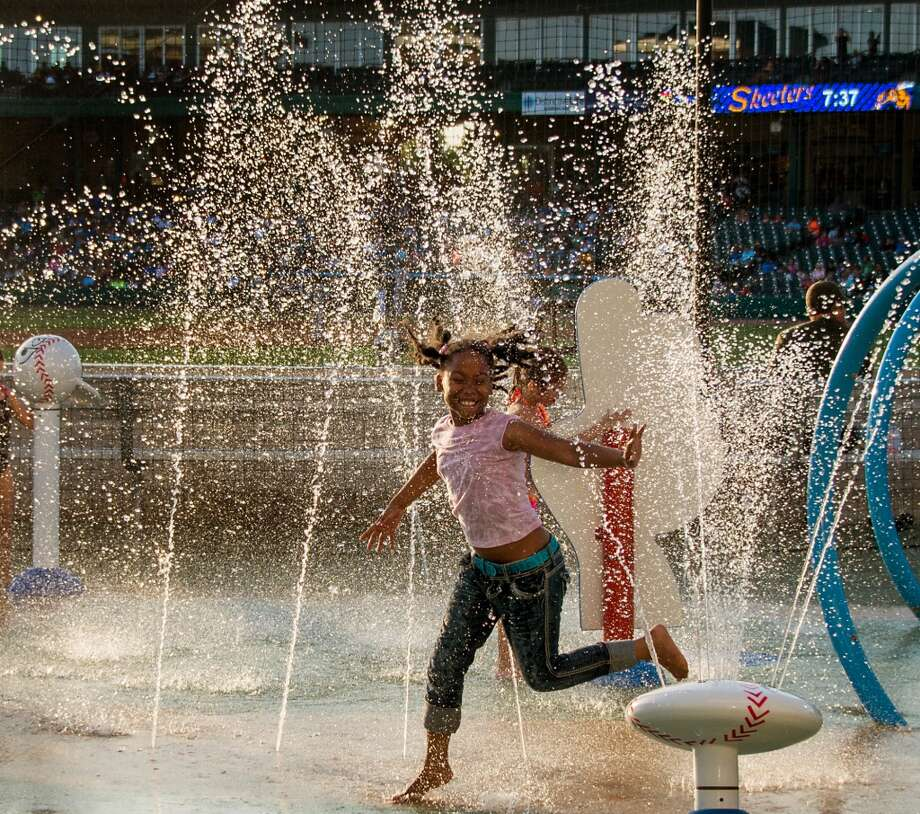 Youngsters enjoy the baseball themed splash pad just over the right field wall. Photo: Smiley N. Pool, Houston Chronicle