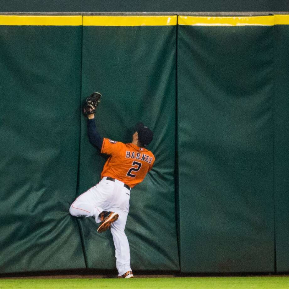 Astros center fielder Brandon Barnes crashes into the fence as he make the catch on a line drive by  Angels catcher Hank Conger during the third inning.