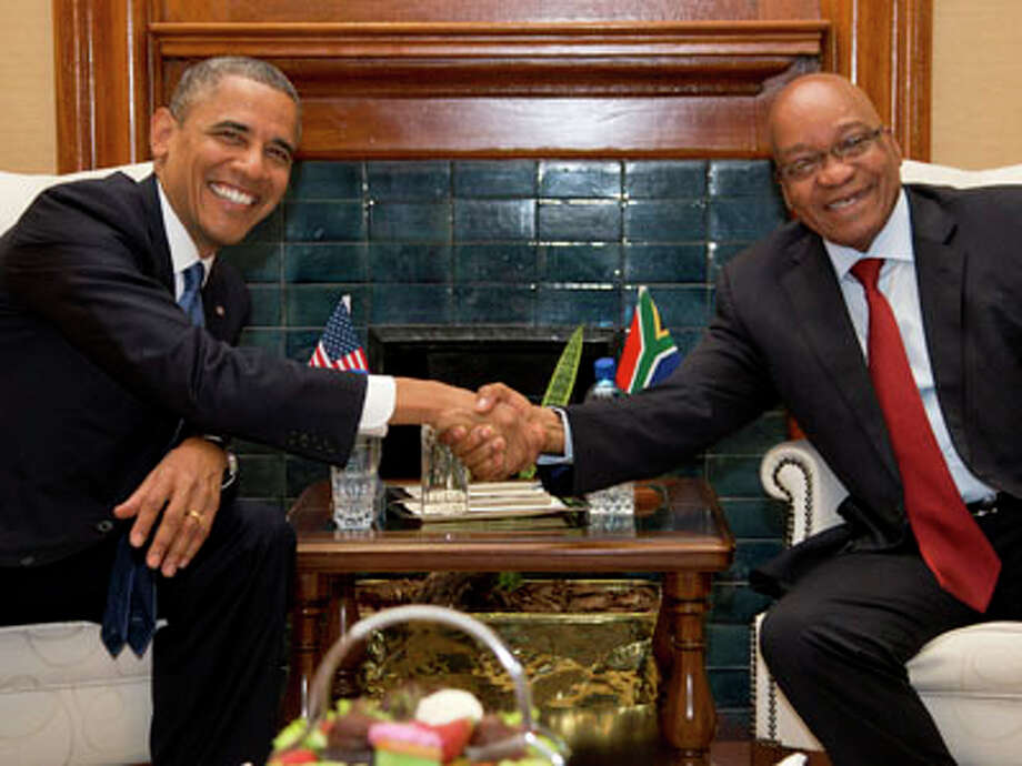 "U.S. President Barack Obama, left, shakes hands with South African President Jacob Zuma at the Union Building on Saturday, June 29, 2013, in Pretoria, South Africa. The visit comes at a poignant time, with former South African president and anti-apartheid hero Nelson Mandela ailing in a Johannesburg hospital.  The White House issued a statement Saturday that President Barack Obama plans to visit privately with relatives of former South African President Nelson Mandela, but doesn't intend to see the critically ill anti-apartheid activist he has called a ""personal hero."" Photo: Evan Vucci, AP / AP"