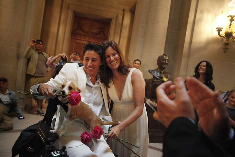 Frances Stevens (left) and Jen Rainin (right ) react after being  married at City Hall by Bevan Dufty (hands at right corner), Director of HOPE, as Punum the dog mouths some flowers while on Stevens lap on Friday, June 28, 2013 in San Francisco,  Calif. Photo: Lea Suzuki, The Chronicle