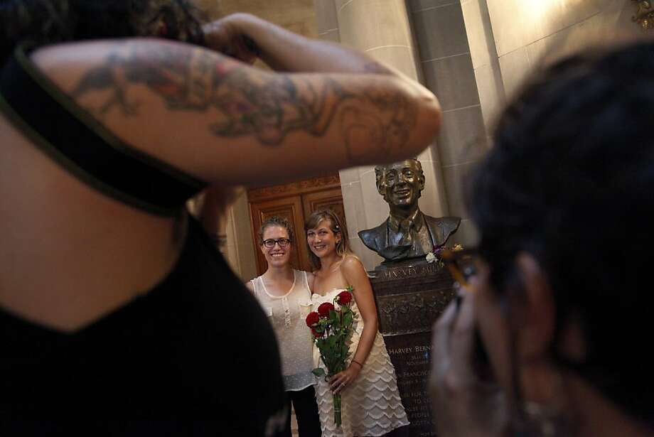 Jacqueline Bialostozky (left) and Jessica Becker pose for a  photo with a Harvey Milk bust after their same-sex marriage at City Hall in San Francisco, Calif., on Friday, June 28, 2013. Photo: Preston Gannaway, Special To The Chronicle
