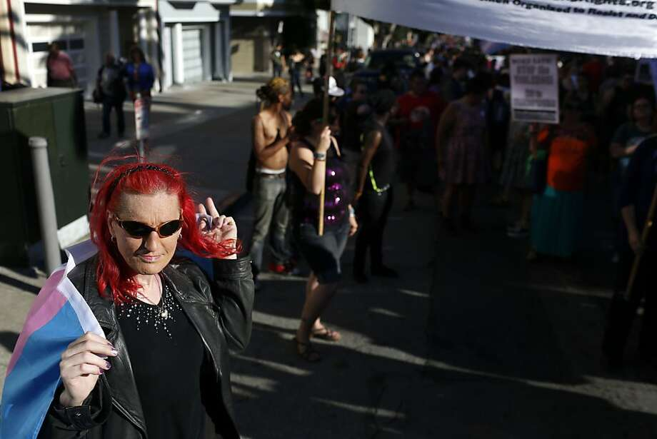 Vicky Zelasky watches the Trans March with a transgender pride flag wrapped around her during the Trans March on Friday in San Francisco. Photo: Ian C. Bates, The Chronicle