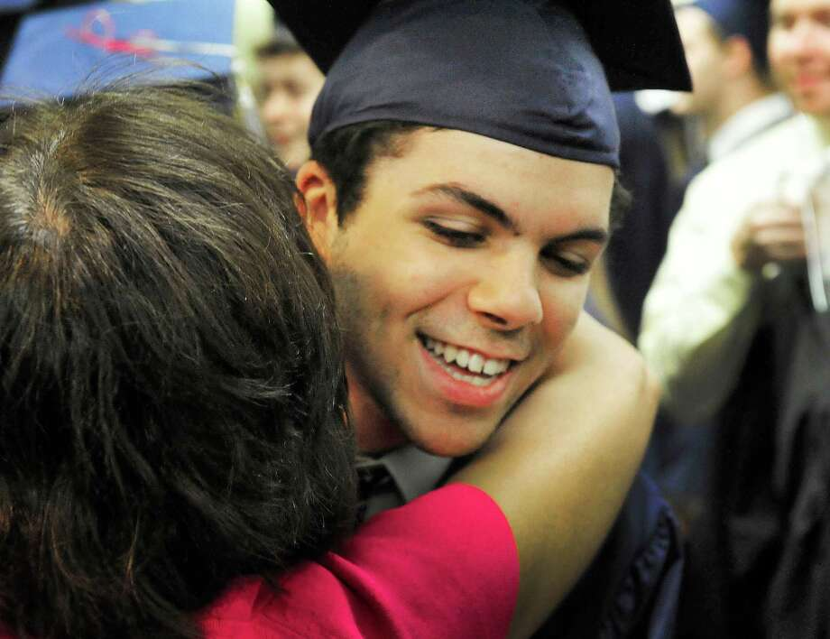 Dillon Damiano gets a hug as New Fairfield High School holds commencement exercises at the O'Neill Center, on the campus of Western Connecticut State University in Danbury, Conn. Saturday, June 29, 2013. Photo: Michael Duffy / The News-Times