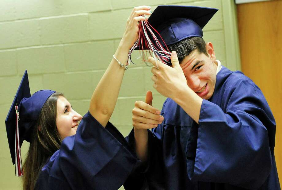 Amanda Gonzalez helps Chris Nuccio with his tassel as New Fairfield High School holds commencement exercises at the O'Neill Center, on the campus of Western Connecticut State University in Danbury, Conn. Saturday, June 29, 2013. Photo: Michael Duffy / The News-Times
