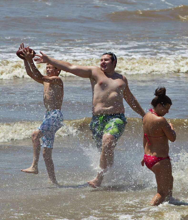 Jacob Barboza, left, and James Martin, both of Spring, play football with friends on the beach along Seawall Boulevard, Saturday, June 29, 2013, in Galveston. Photo: Nick De La Torre, Houston Chronicle / © 2013  Houston Chronicle