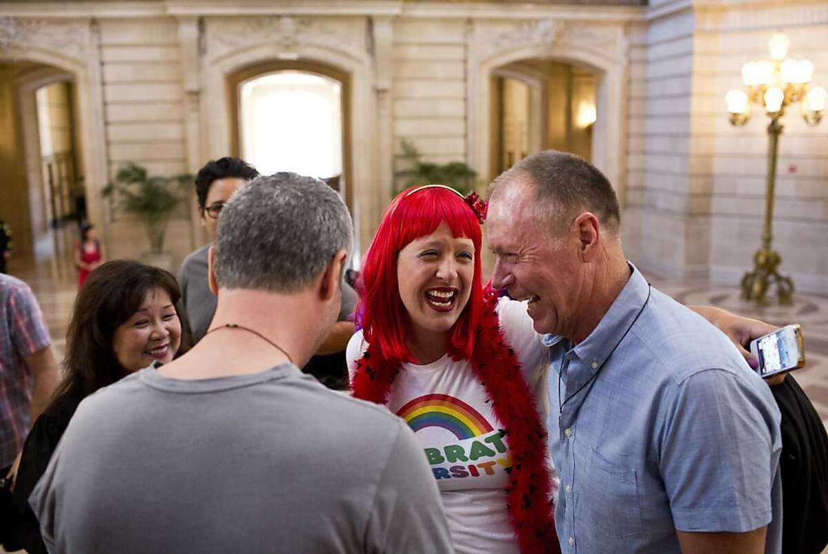 Brandie Yelland, a borrowed witness, congratulates Brian Nolan and Art Cook, of Belmont, after they married in the rotunda at City Hall in San Francisco, Calif., Saturday, June 29, 2013.