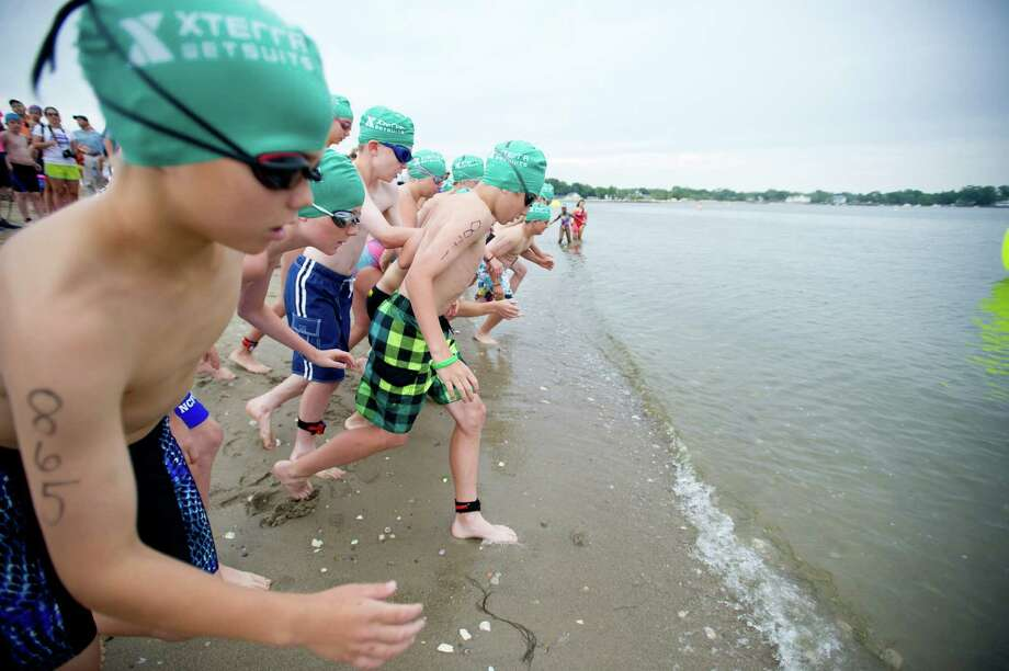 Kids compete in the swimming portion of Saturday's KIC-IT kid's triathalon at Cove Island Park on June 29, 2013. Photo: Lindsay Perry / Stamford Advocate