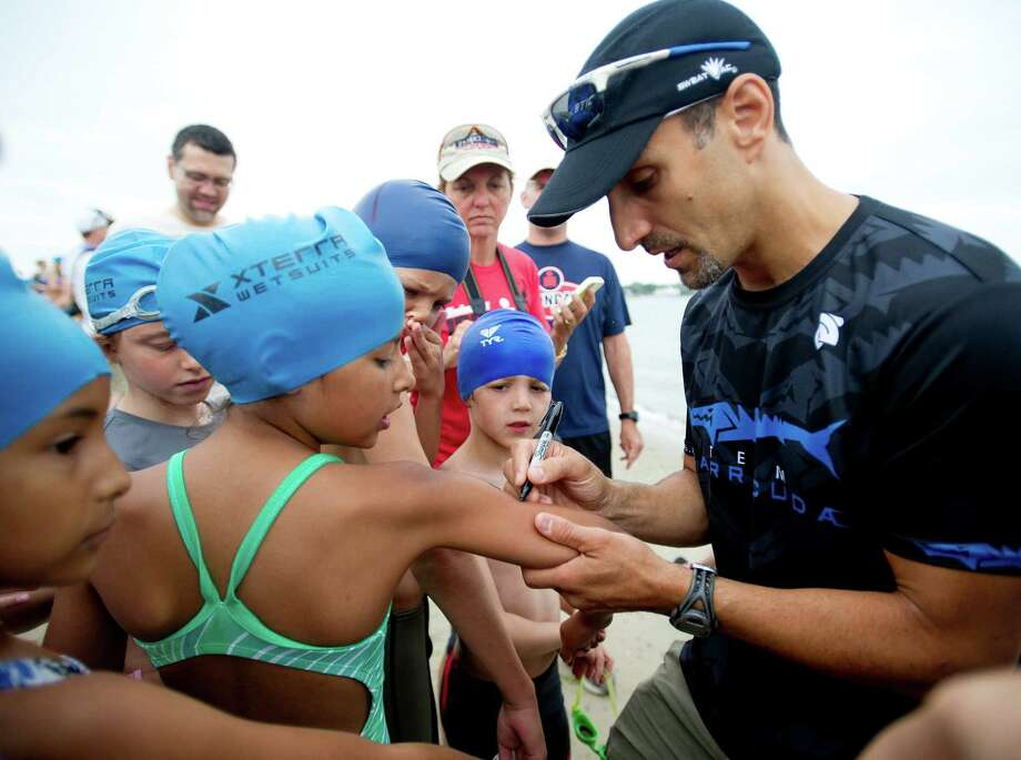 Kids get their numbers written on their arms before competing in Saturday's KIC-IT kid's triathalon at Cove Island Park on June 29, 2013. Photo: Lindsay Perry / Stamford Advocate