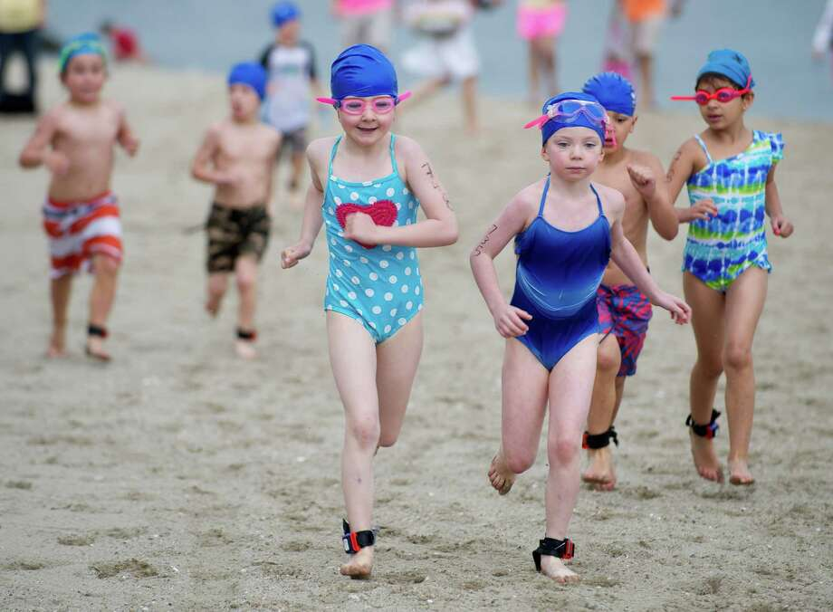 Kids exit the water and run to their bikes as they compete in Saturday's KIC-IT kid's triathalon at Cove Island Park on June 29, 2013. Photo: Lindsay Perry / Stamford Advocate