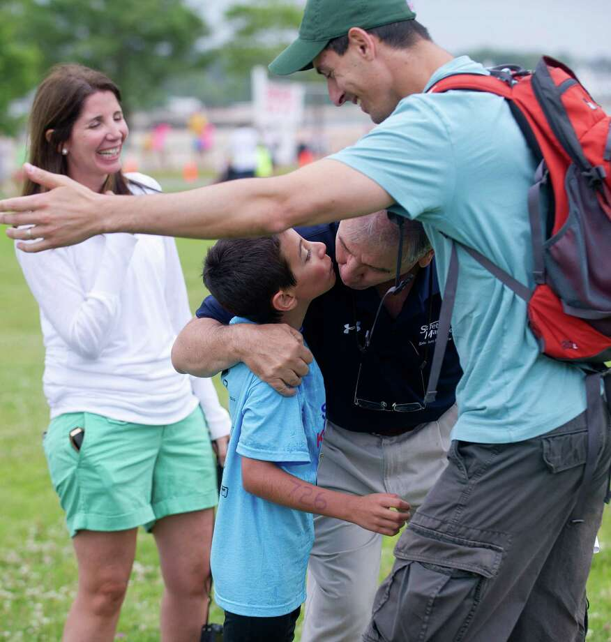 Chris Gervasi, 7, is congratulated by his family after he crossed the finish line at the end of Saturday's KIC-IT kid's triathalon at Cove Island Park on June 29, 2013. Photo: Lindsay Perry / Stamford Advocate